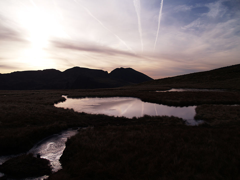 Scafell and Scafell Pike with the rising sun across Kirkfell Tarn