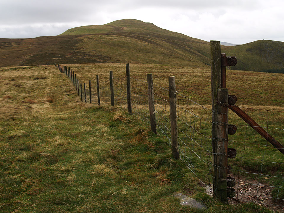 The summit of Burnbank Fell is marked by the straining post on the right looking back to Blake Fell