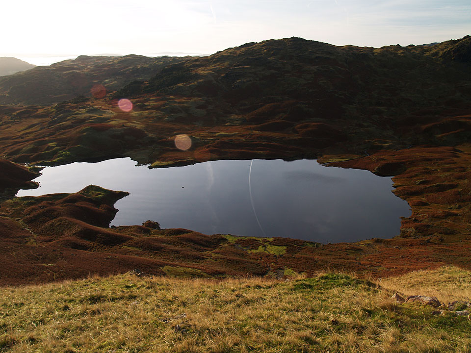 Easedale Tarn with reflected contrail from Tarn Crag