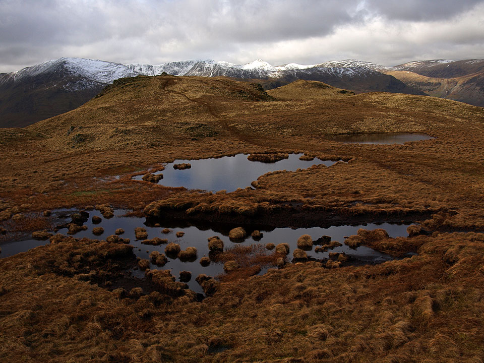 The bejewelled summit of Brock Crags with Helvellyn beyond the cairn