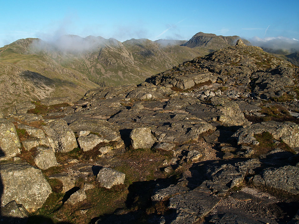 Mist over Crinkle Crags with Bowfell beyond the main summit cairn