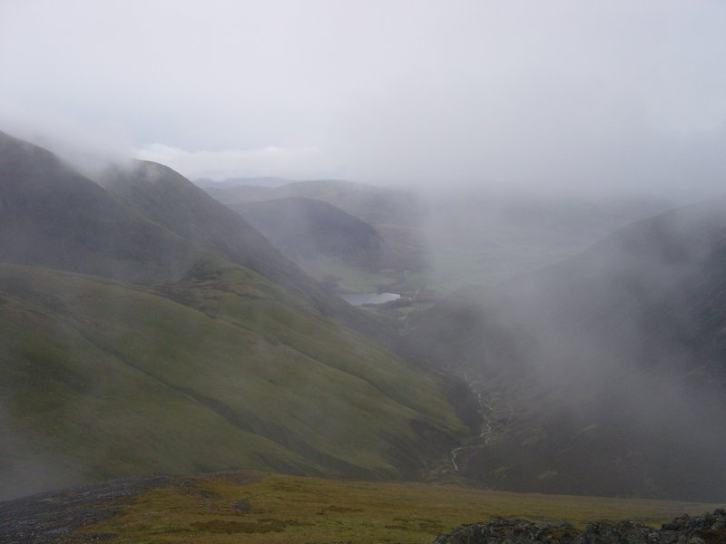 The clouds clear momentarily on Sand Hill to allow a glimpse of Crummock Water and Mellbreak, Grasmoor is to the left.